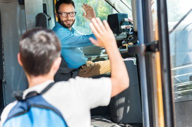 handsome smiling bus driver greeting schoolboy who entering bus
