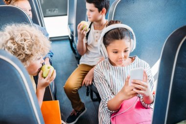 adorable little schoolgirl using smartphone and listening music with headphones while riding on school bus with classmates