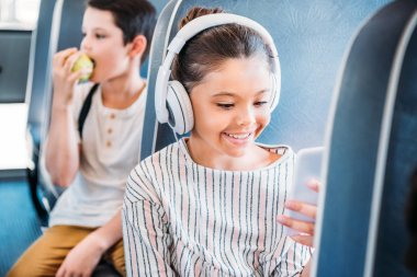 happy little schoolgirl using smartphone and listening music with headphones while riding on school bus