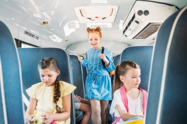 adorable little pupils riding on school bus during excursion
