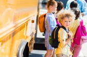Fotografie adorable curly schoolboy with his classmates standing near school bus