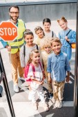 Fotografie view from school bus at group of schoolchildren with traffic guard looking at camera