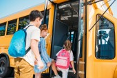 rear view of pupils with backpacks entering school bus