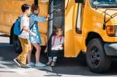 Fotografie učenci relaxační poblíž školní autobus na parkovišti