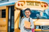 boldog kis iskolás a notebook nézi a kamera előtt iskolabusz