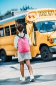 zadní pohled na školačka s batoh stojící před školní autobus