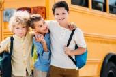 Photo happy little schoolboys embracing in front of school bus