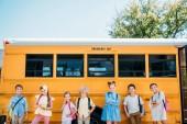 Fotografia gruppo di allievi adorabili in posa davanti allo scuolabus