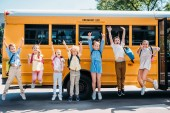 Fotografie group of happy pupils jumping in front of school bus and looking at camera