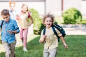 Fotografie Glücklicher Schüler mit Klassenkameraden im Schulgarten
