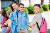 Fotografie group of adorable schoolchildren spening time together after school