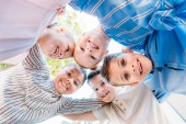 Fotografie bottom biew of group of smiling schoolchildren standing in circle and looking at camera