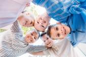dolní biew skupiny usmívající se školní děti stojí v kruhu a při pohledu na fotoaparát
