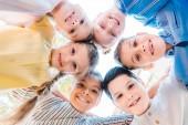 dolní biew skupiny šťastné děti stojí v kruhu a při pohledu na fotoaparát