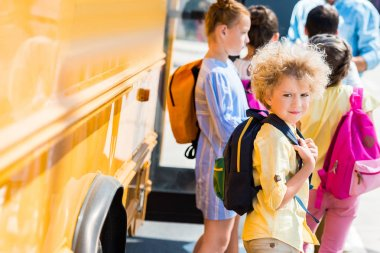 adorable curly schoolboy with his classmates standing near school bus