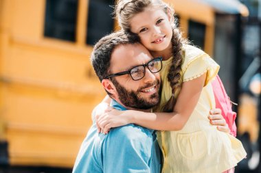 father embracing his little daughter in front of school bus