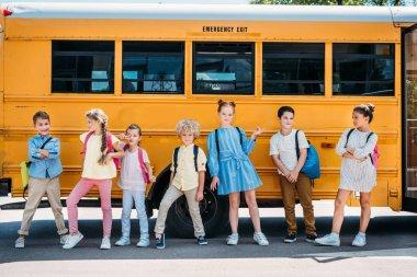 Group of happy pupils posing in front of school bus stock vector