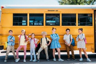 group of adorable schoolchildren posing in front of school bus