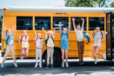 Group of happy pupils jumping in front of school bus and looking at camera stock vector