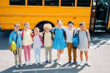 group of adorable schoolchildren standing in front of school bus and looking at camera