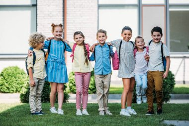 group of adorable schoolchildren standing at school garden and looking at camera