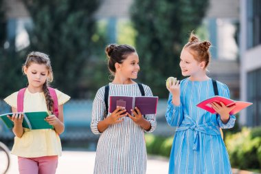 adorable schoolgirls with notebooks spending time together after school