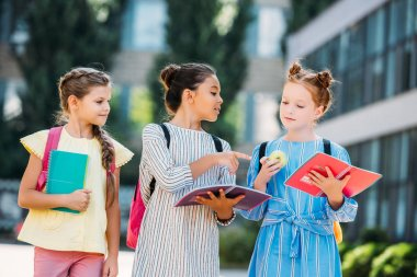 Schoolgirls with notebooks spending time together after school and discussing homework stock vector