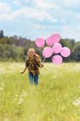 Veselý kluk s růžové bubliny v ruce běží v louce
