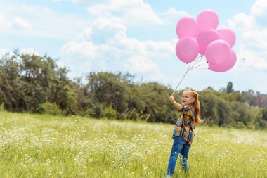 Adorable child with pink balloons standing in summer field with blue sky on background stock vector