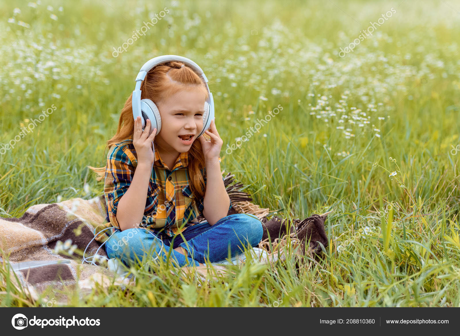 cute kid listening music headphone while sitting blanket field wild