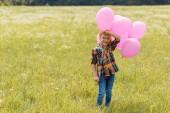 šťastné dítě s růžové bubliny v létě pole