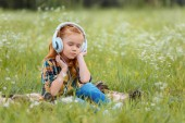 little kid with eyes closed listening music in headphones while resting on blanket in meadow