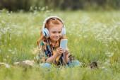 Fotografie usmívající se dítě v sluchátka pomocí chytrého při odpočinku na dece v louce s divokými květy