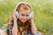 portrait of smiling kid listening music in headphones with green grass on background