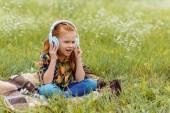roztomilé dítě poslech hudby do sluchátek, zatímco sedí na dece v poli s divokými květy