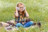 Fényképek cute kid listening music in headphone while sitting on blanket in field with wild flowers