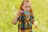 Fotografie portrét dítě vyfukuje mýdlové bubliny v louce