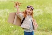 Fotografie portrét malé dítě v pilotní kostýmu s dřevěná hračka letadlo stojící v louce
