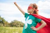 imádnivaló gyermek a szuperhős jelmezben kinyújtott karját, nyári mező