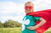 Fényképek portrait of little child in red superhero costume standing akimbo in summer meadow