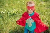 aranyos gyermek piros szuperhős maszk és cape állandó nyári területén