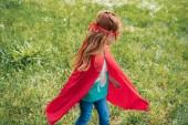piccolo bambino in costume del supereroe rosso in piedi nel campo di estate