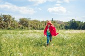 little kid in red superhero cape and mask running in meadow on summer day