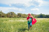 Fényképek vidám gyerek piros szuperhős cape és a nyári rét futó maszk