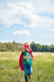 Fényképek little kid in red superhero cape and mask with outstretched arm running in meadow on summer day