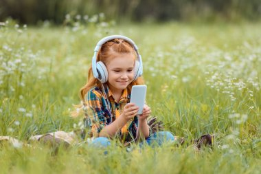 smiling child in headphones using smartphone while resting on blanket in meadow with wild flowers