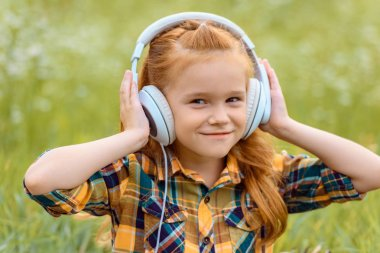Portrait of smiling kid listening music in headphones with green grass on background stock vector