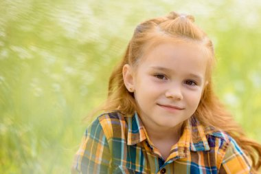 portrait of adorable kid looking at camera with blurred green grass on background