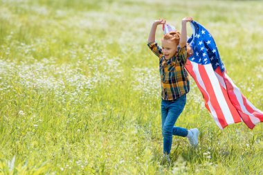 happy child running in field with american flag in hands
