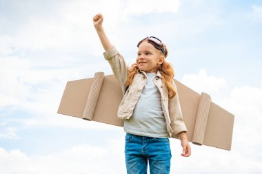 Portrait of child with paper plane wings on back and protective eyeglasses on head standing with outstretched arm against blue cloudy sky stock vector
